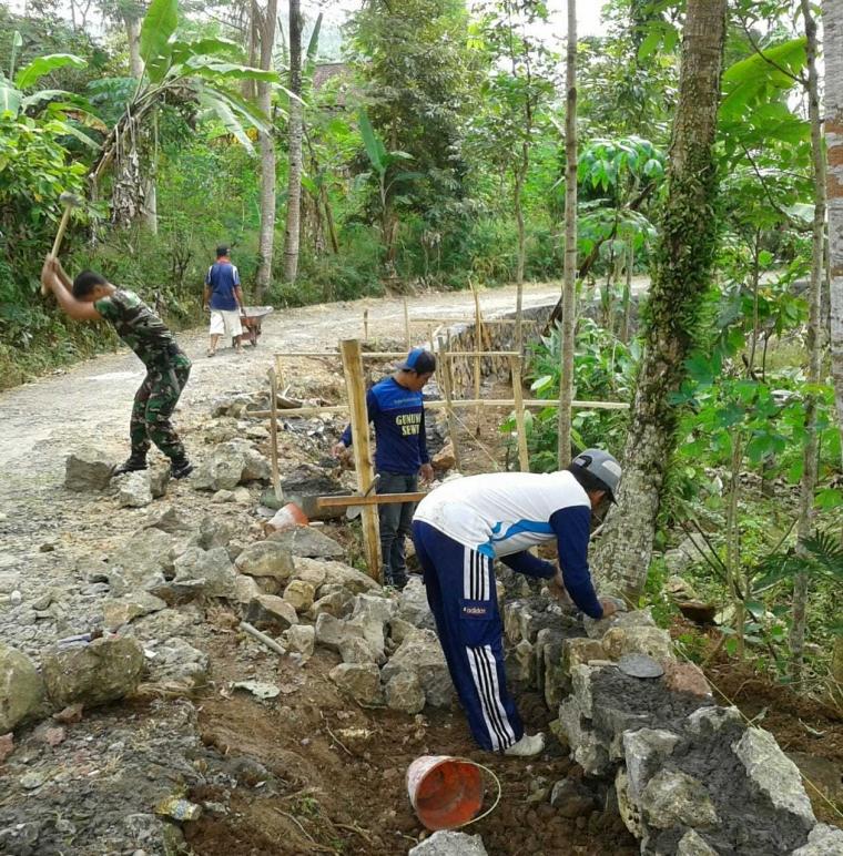 Babinsa Pos Ramil Suruh Bantu Warga dalam Pembuatan Talud Penahan Jalan