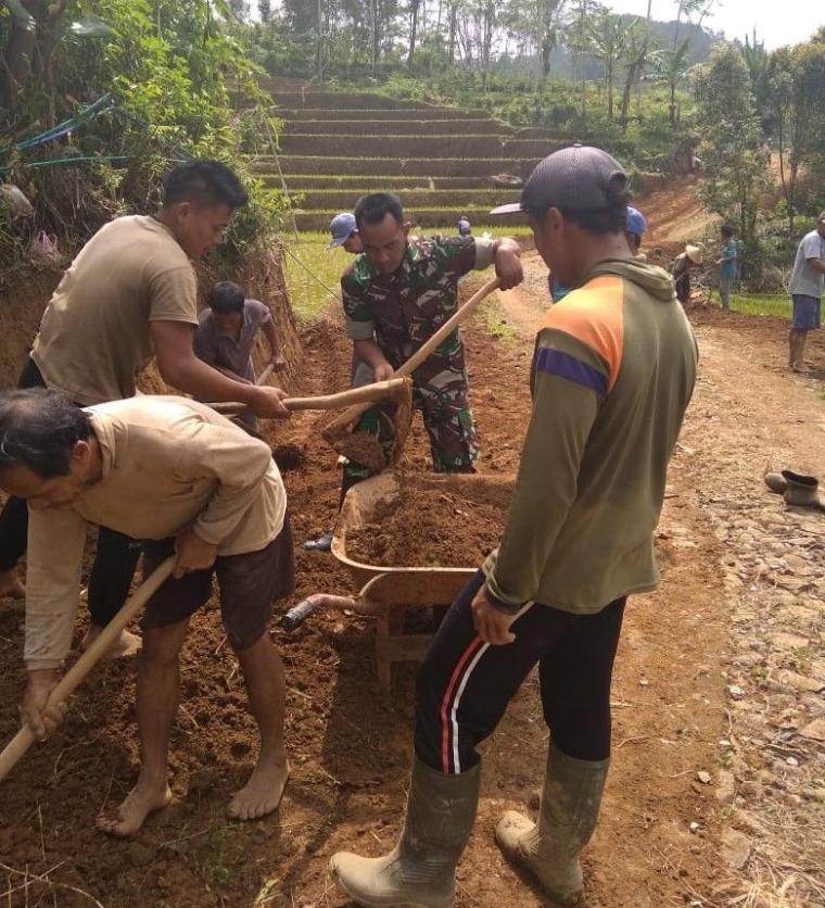 Babinsa Desa Salamwates Serda Harianto Bantu Warga Karya Bakti Pelebaran Jalan